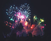 Crowd of People Watching a Colorful Fireworks Display for New Years or Fourth of July Celebration Event
