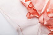 Shiny pink satin ribbon with transparent fabric on white background