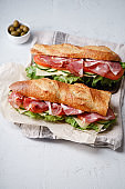 Side view of two fresh baguette sandwiches bahn-mi styled. Ham, sliced cheese, tomatoes and fresh lettuce, styled on concrete background.