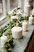 burning candles near green branches