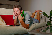 lifestyle indoors portrait of young attractive and happy man lying at home sofa couch relaxed using internet on laptop computer watching online movie or working as independent freelancer