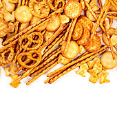 Salty crackers, sticks, pretzels, and goldfishes, shot from above on a white background with copy space. Party snacks mix with a place for text