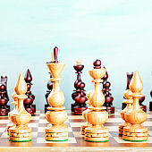 Vintage chess figures on a board at the very beginning of the game, with copy space