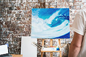 Painter stands in front of the easel with a canvas and considers his work. Artist workspace in studio