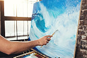 Male hand of artist holding paintbrush on background of canvas on easel. Professional painter drawing ocean wave in loft studio. Hobby concept