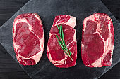 Three slices of raw meat on black with copy space