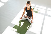 Top view of fitness woman practies yoga lotus poses in white sunny gym early morning. Young athletic woman doing yoga exercise on fitness mat