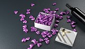 Red Wine Bottle With Opened Gift Box Full Of Purple Hearts