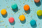 Top view of scattered colorful macaroons and sugar sprinkles over blue background. Abstract food background.