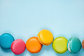 Colorful macaroons arranged over blue background. Copy space.