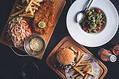 Table de Restaurant avec un Fish and Chips, Hamburger et Frites, Plat de Pâtes