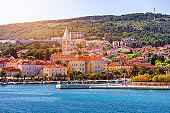 Supetar city in Brac island, Croatia. View from the sea. Picturesque scenic view on Supetar on Brac island, Croatia. Panoramic view on harbor of town Supetar from the side of sea. Brac, Croatia.