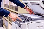 Close-up business man Hand press button on panel of printer, printer scanner laser office copy machine supplies start concept.