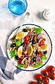 Tuna salad with white beans, tomatoes, boiled eggs and black olives