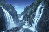 Mystery night at deep tropical forest with flowing waterfall. Fantasy landscape.