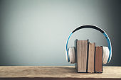 Headphones and books on wooden table. Audio book concept