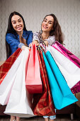 Two happy beautiful and smiling girlfriends with bright shopping bags
