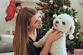 Beautiful woman with her dog enjoying Christmas eve/New Year.