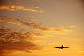 Flying commercial passenger airplane over sunset sky