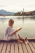 Pretty woman enjoying on the lake and reading a book.