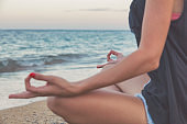 Young woman practicing yoga on the tropical beach.