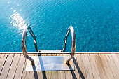 Grab bars ladder in swimming pool on the deck floor