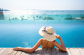 Portait of asian woman relaxing in swimming pool with sunbathe
