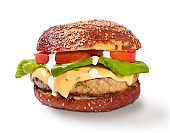 Grilled hamburger with white sauce lettuce tomato isolated on white