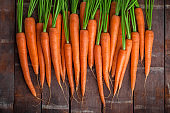 Carrot arrangement overhead lined up on brown rustic wooden table