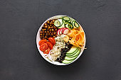Vegetarian buddha bowl. Clean and balanced healthy food concept. Rice, spicy chickpeas, black and white quinoa, avocado, carrot, zucchini, radish, tomatoes on dark background, top view