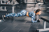 Healthy young Women Doing Planking Exercise in gym. Fitness, workout concept. Copyspace