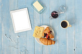 Top view breakfast table with white tablet, coffee, croissants, cheese and jam in home kitchen