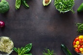 Frame from set of ingredients for detox salad on dark background. Broccoli, spinach, avocado, arugula, pea shoots, alfalfa, onion, tomatoes and cucumber on dark background, top view