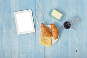 White tablet in home kitchen with croissants, jam, cheese, butter and coffee, top view. Breakfast table concept