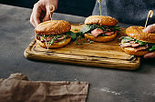 Mens hands holding hold a wooden board with burgers with grilled meat