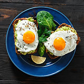 Top view healthy avocado toasts fried egg cheerful faces Healthy breakfast table
