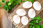 Fresh white raw chicken eggs with parsley on an old wooden table.