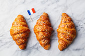 Croissants with French flag. Marble background. Top view.