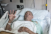 Elderly Man Medical Patient Waving From a Hospital Ward Bed