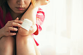 Asian woman with hand injury bandaging wound