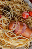 Spaghetti with spices and frozen tomatoes on a plate. Part of the frame