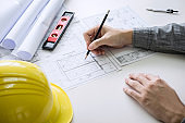 Construction engineering or architect hands working on blueprint inspection in workplace, while checking information drawing and sketching for architecture project working