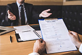 Employer or recruiter holding reading a resume during about his profile of candidate, employer in suit is conducting a job interview, manager resource employment and recruitment concept