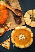 Pumpkin squash Soup served in mini pumpkin bowl / Thanksgiving food,top view