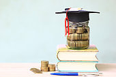 Graduation hat on the glass bottle and books on white background, Saving money for education concept
