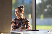 Young female girl student having coffee break in glass interior