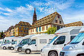 Motorhomes parked in a row on background traditional colorful houses in La Petite France, Strasbourg