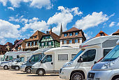 Close up motorhomes parked in a row on background traditional colorful houses in La Petite France, Strasbourg