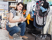 Happy woman holding dog and choosing clothes