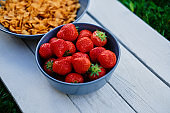 Delicious strawberry with corn flakes on a wooden desk.
